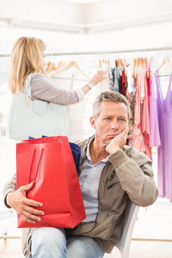 Bored man die op zijn winkelende vrouw wachten stock foto