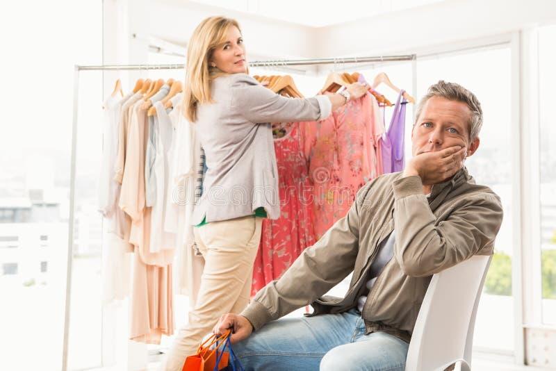 Bored man die op zijn winkelende vrouw wachten stock afbeelding