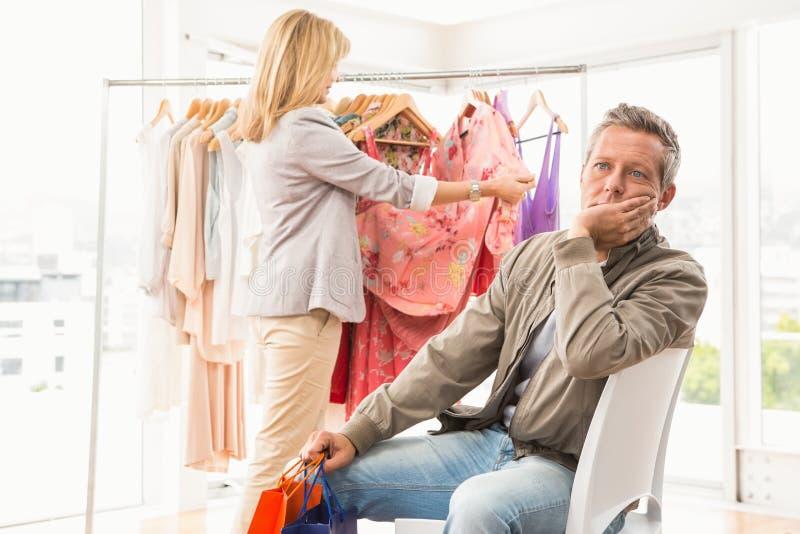 Bored man die op zijn winkelende vrouw wachten stock foto's