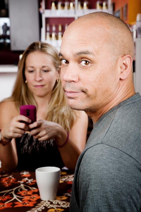 Bored man met vrouw op celtelefoon royalty-vrije stock foto