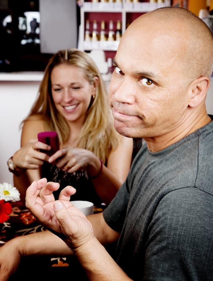 Bored man met vrouw op celtelefoon stock foto