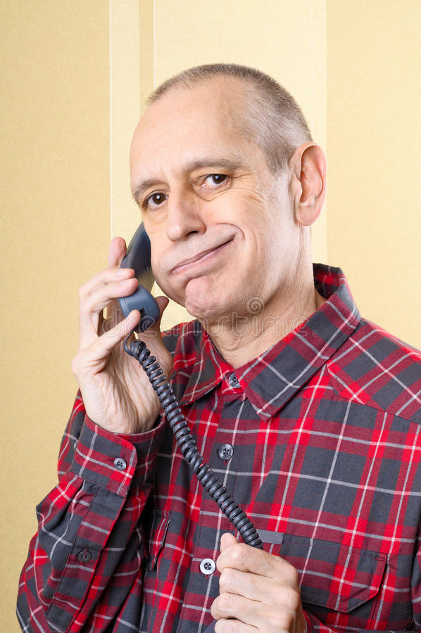 Bored Man on Phone. Annoyed man listening a boring conversation on phone stock photography