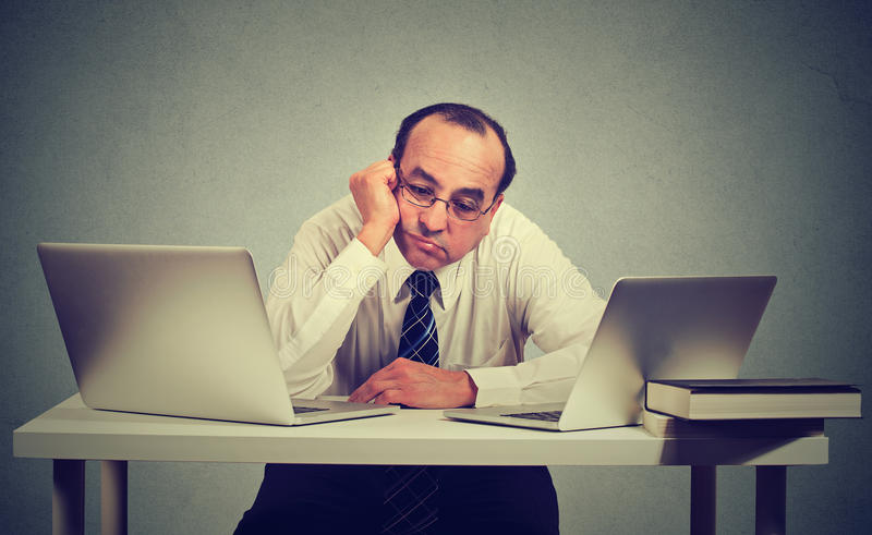 Bored man sitting in front of two laptop computers. Bored business man sitting in front of two laptop computers stock images