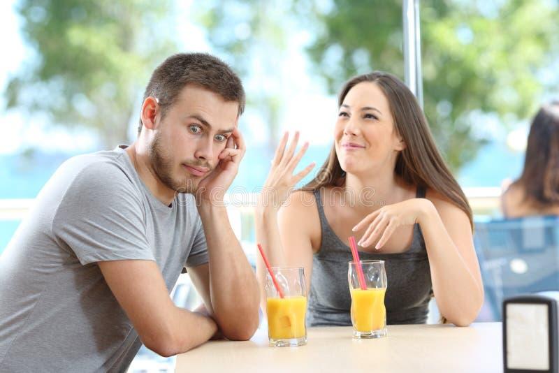 Bored man som lyssnar på hennes vän och pratar i en bar arkivfoto
