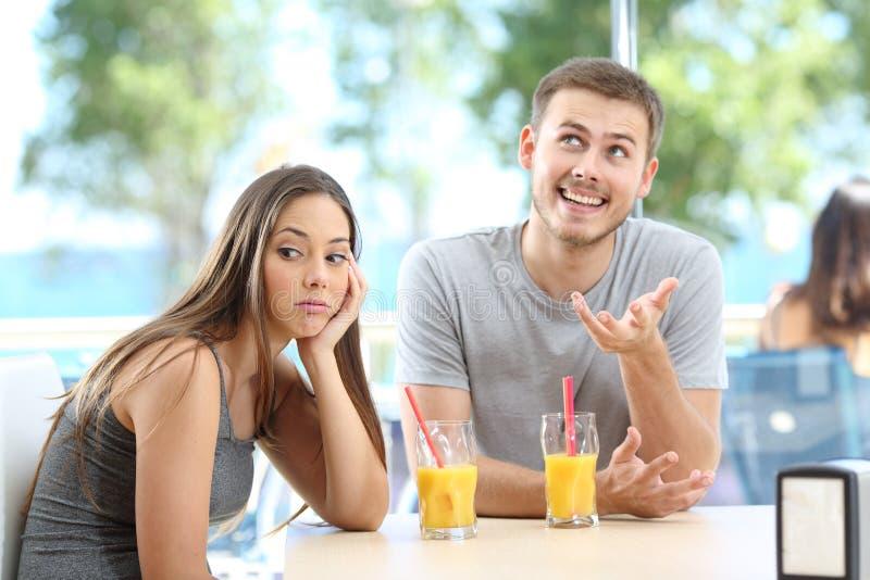 Bored meisje die een slecht gesprek van een vriend of een partner luisteren stock foto's