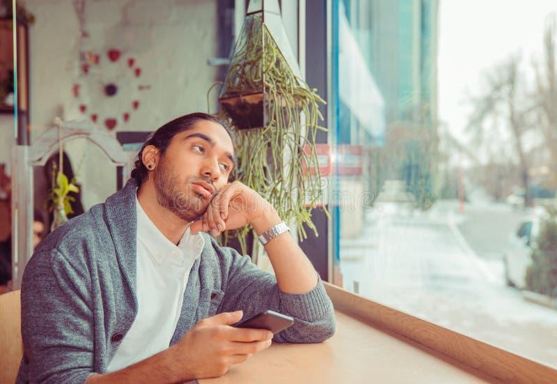 Bored mens die omhoog vermoeid houdend telefoon in hand kijken royalty-vrije stock foto
