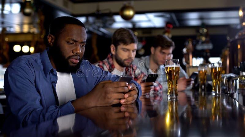 Bored mensen die telefoons in bar scrollen die levende mededeling, gadgetverslaving vervangen stock afbeelding