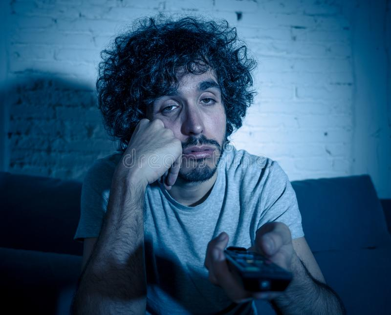 Lifestyle portrait of young millennial man watching boring tv feeling sleepy at night royalty free stock photography