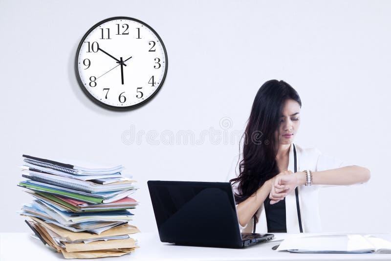 Bored onderneemster die horloge bekijken stock foto's