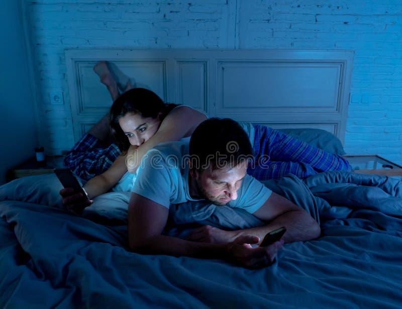 Bored paar in bed wijdde zich aan hun slimme mobiele telefoons negerend elkaar laat bij nacht royalty-vrije stock afbeelding