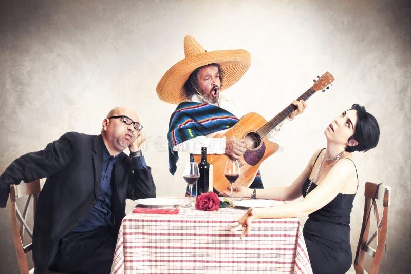 Bored paar bij diner oblyed om aan een Mexicaanse musicus te luisteren royalty-vrije stock afbeeldingen