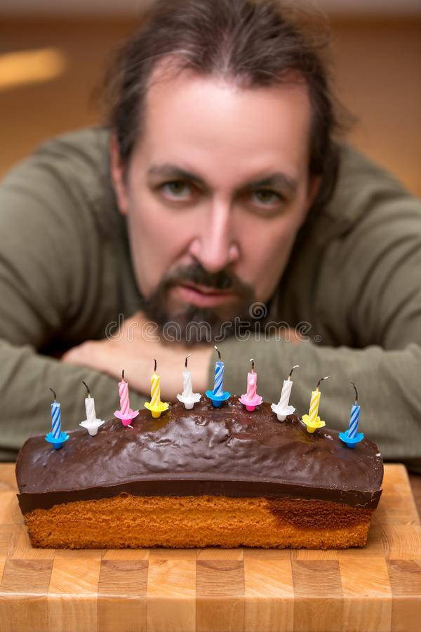 Bored or looking man behind a marble cake. With blown out candles royalty free stock photos