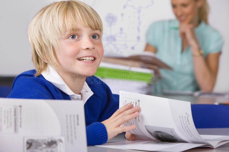 Bored school boy reading workbook in classroom royalty free stock photography