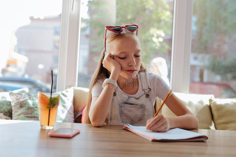 Bored schoolgirl feeling tired while doing homework royalty free stock photos