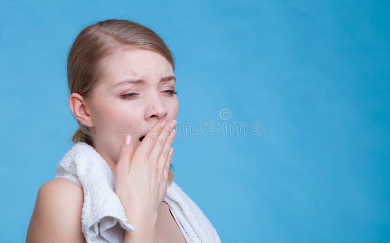 Bored slaperige vrouw die terwijl het houden van handdoek geeuwen stock foto's