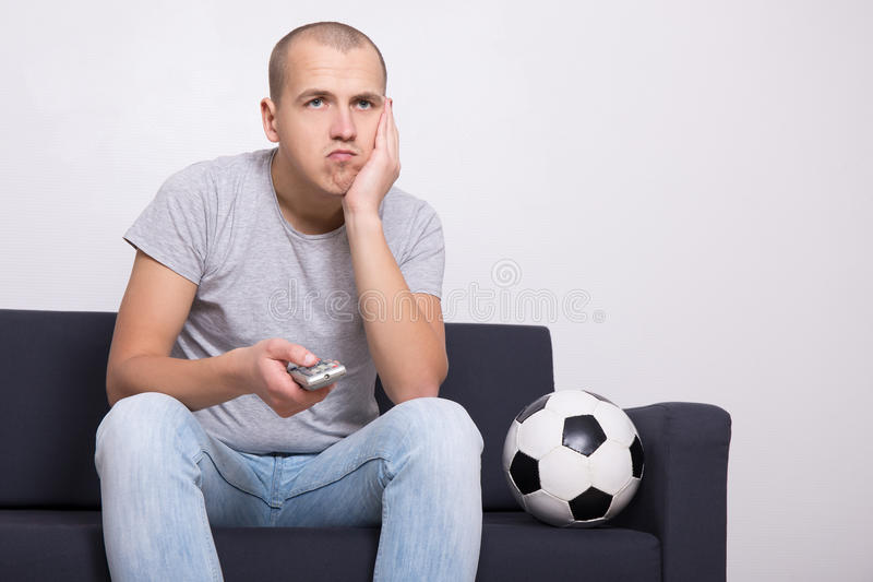 Bored soccer fan with ball watching game on tv. At home royalty free stock photography