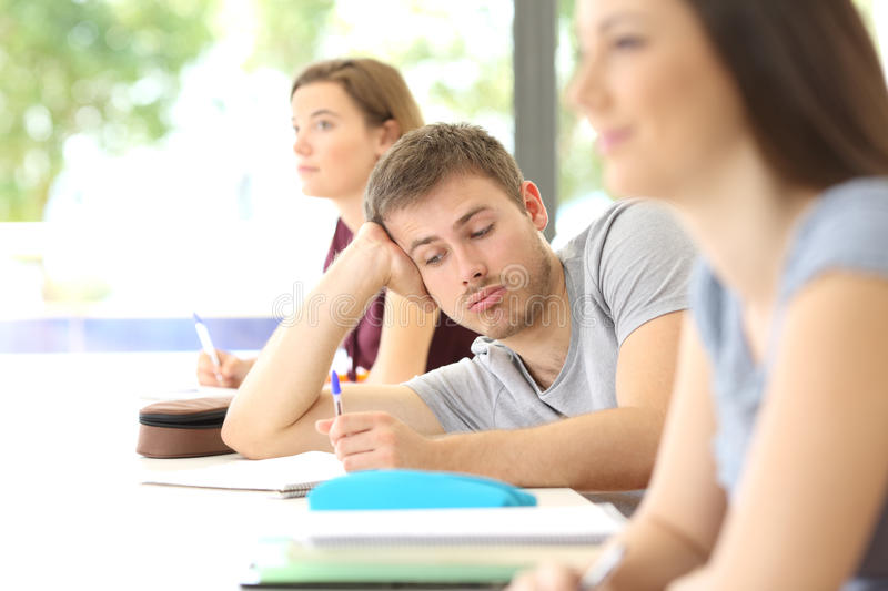 Bored student distracted during a class at classroom. With classmates in the background royalty free stock images