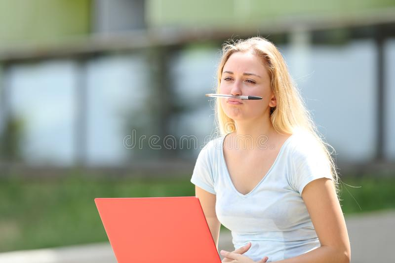 Bored student distracted playing with a pen. Outdoors in a campus royalty free stock photography
