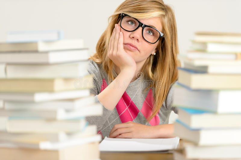Bored student girl between stack of books royalty free stock photography