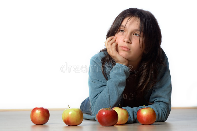 Bored Teen. A bored teenaged girl props her head up with her hand behind 5 apples royalty free stock photos