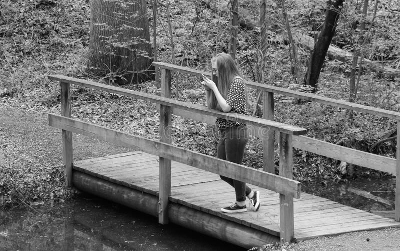 Bored Teen B&W. Young teen girl on a wooden bridge bored and on her device stock images