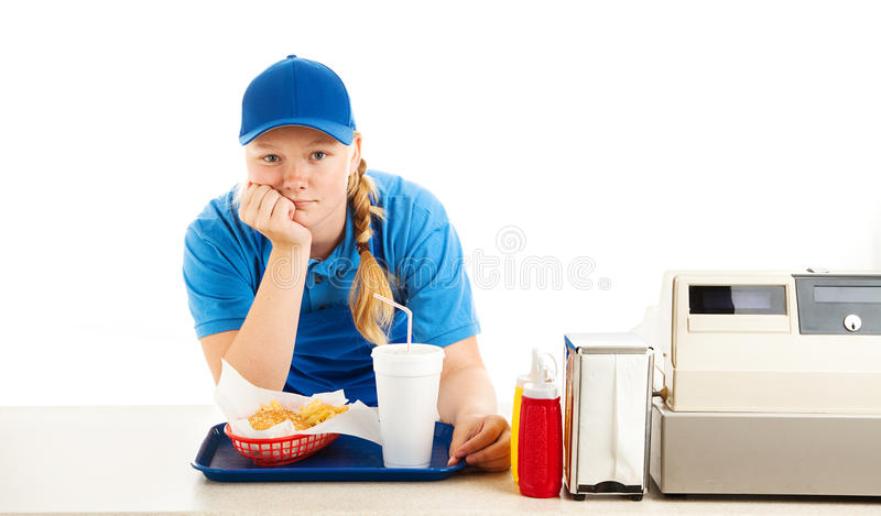 Bored Teen Fast Food Worker. Teenage worker in a fast food restaurant bored and leaning on the counter. White background royalty free stock photo
