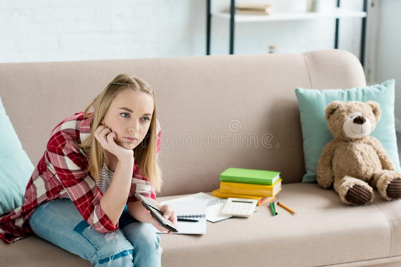 Bored teen student girl with remote control watching tv while sitting on couch with book. And notes stock image
