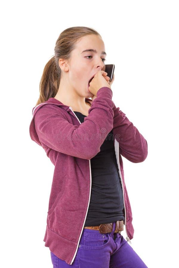 Bored teenage girl speaking on mobile phone, yawning, isolated o stock image