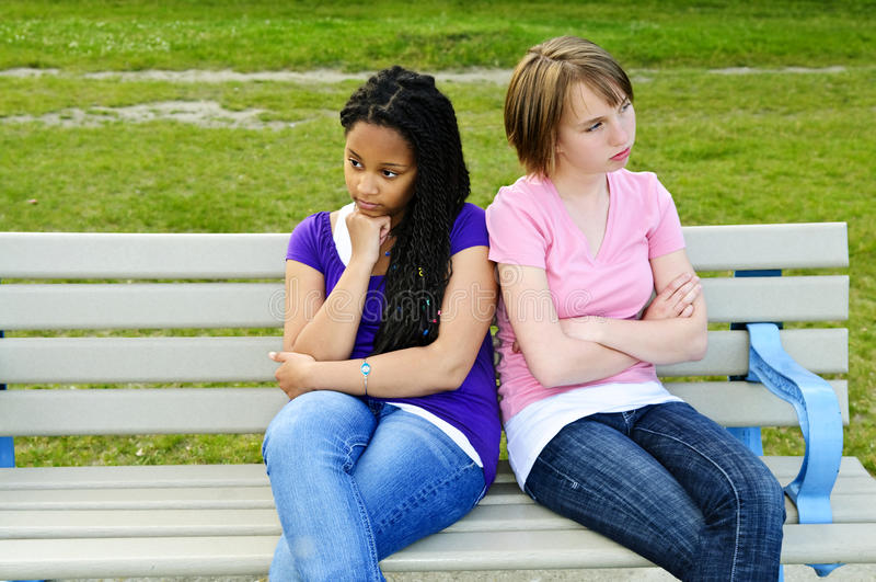 Bored teenage girls. Two bored teenage girls sitting on bench royalty free stock photos