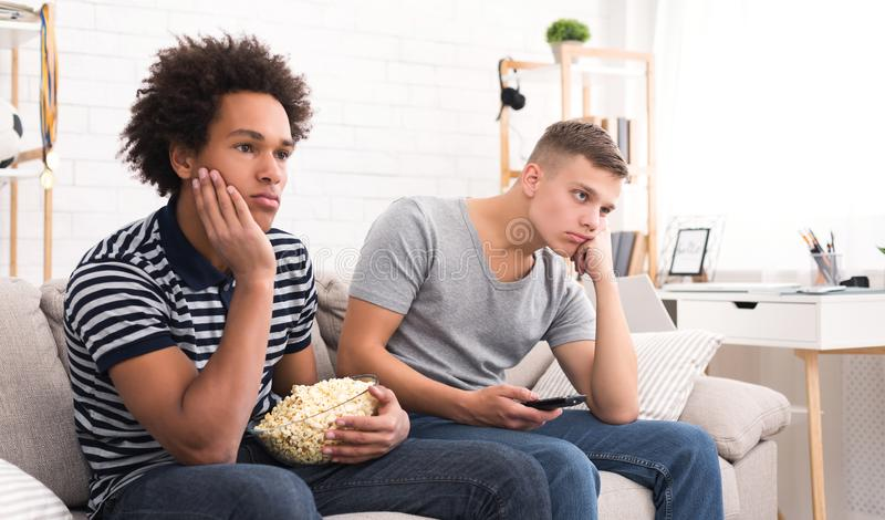 Bored teens watching dull movie with popcorn. At home, copy space stock image