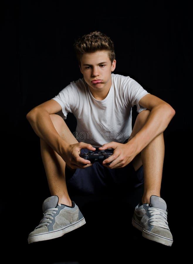 Bored of teleurgestelde jongen het spelen videospelletjes royalty-vrije stock foto