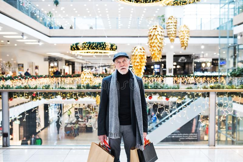 A bored and tired senior man with paper bags in shopping centre at Christmas time. A portrait of bored and tired senior man with paper bags standing in shopping stock image