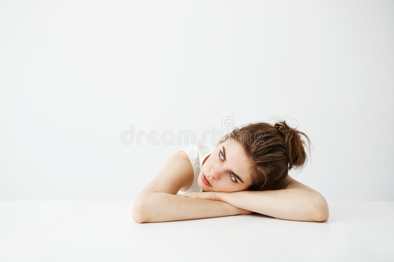 Bored tired young pretty girl with bun thinking dreaming lying on table over white background. stock photo