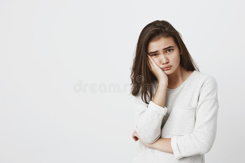 Bored tired youngbrunette female wearing her dark hair loose, frowning face in dissatisfaction, keeping hand on cheek. Bored tired youngbrunette female wearing royalty free stock photography