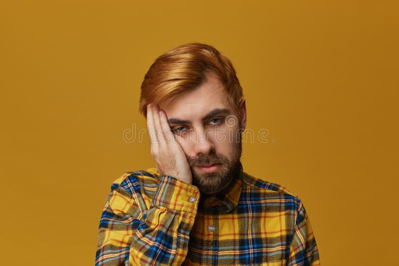 Bored to death! Young handsome male with dyed hair feels sad, lonely and boring. royalty free stock image