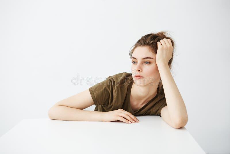 Bored vermoeide saaie jonge studente met broodjeszitting bij lijst over witte achtergrond stock foto's