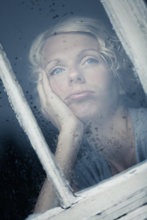 Bored Vrouw die het Regenachtige Weer door het Venster bekijken stock foto