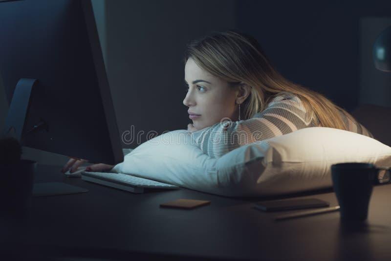 Bored vrouw die laat bij nacht met haar computer werken stock fotografie