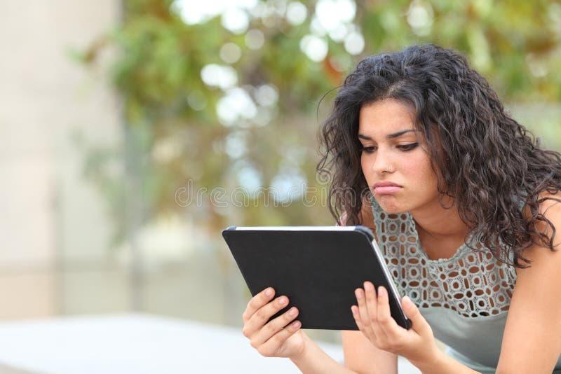 Bored vrouw het letten op media in een tablet in een park stock foto
