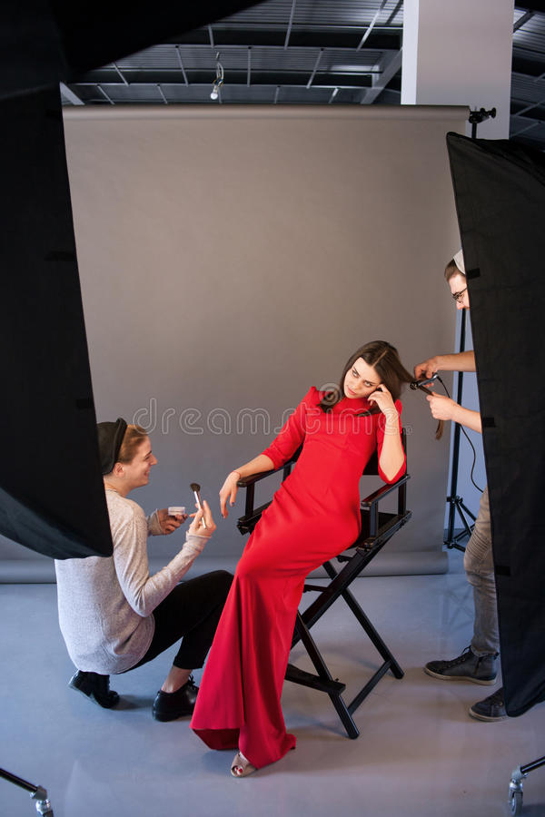 Bored vrouw wacht het eind van make-up en het hairstyling royalty-vrije stock afbeelding