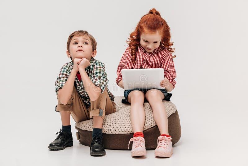 bored weinig jongen die omhoog terwijl glimlachende vriend gebruikend digitale tablet kijken royalty-vrije stock fotografie