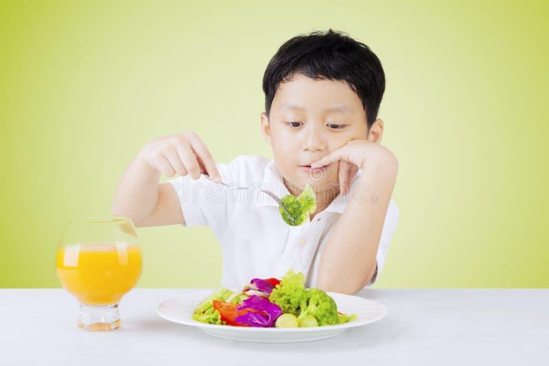 Bored weinig jongen plukt salade royalty-vrije stock afbeeldingen
