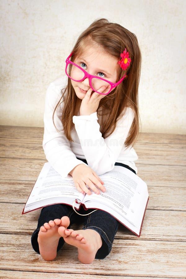 Bored weinig schoolmeisje die glazen dragen en boek lezen stock afbeeldingen