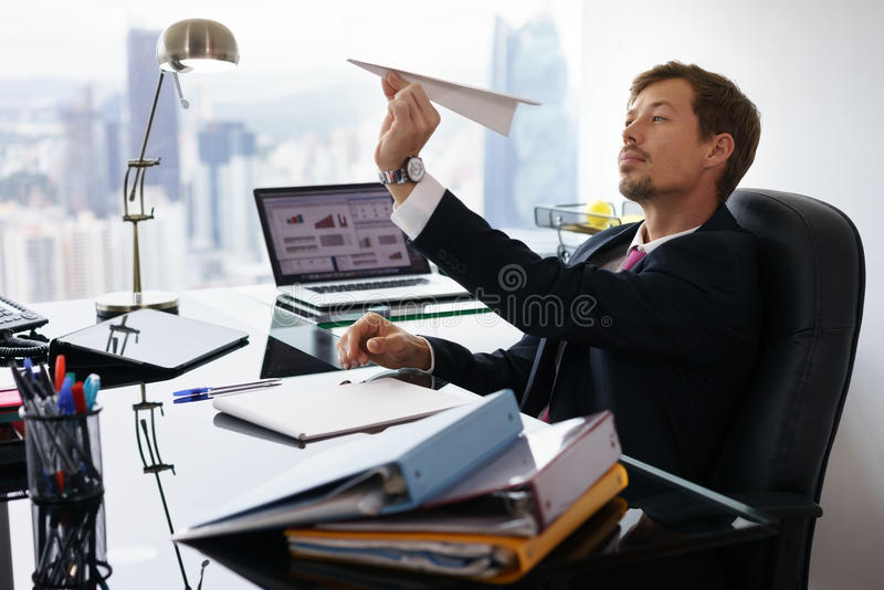 Bored White Collar Worker Throwing Paper Airplane In Office stock photo
