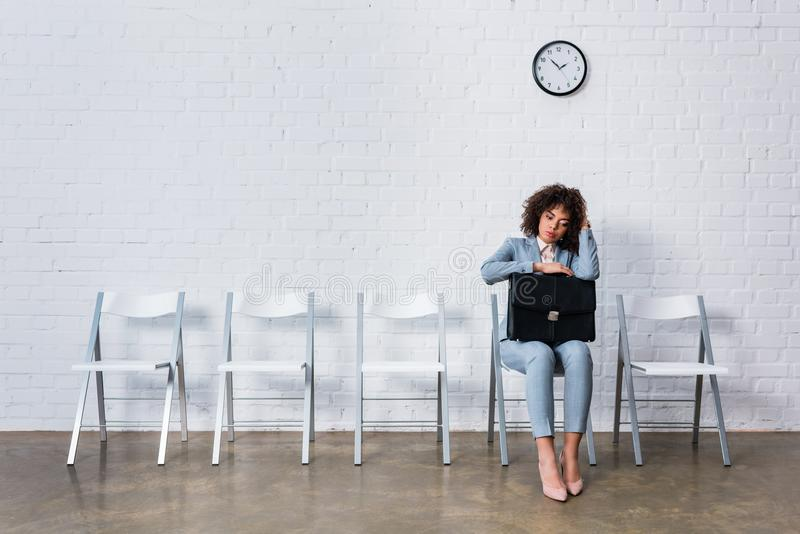 Bored woman with briefcase sitting on chair stock photo