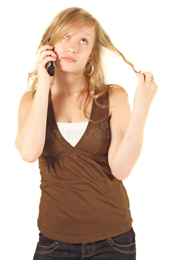 Bored woman on cellphone. A studio view of a young woman appearing bored and disinterested, twirling and twisting her blond hair during a conversation on her royalty free stock images