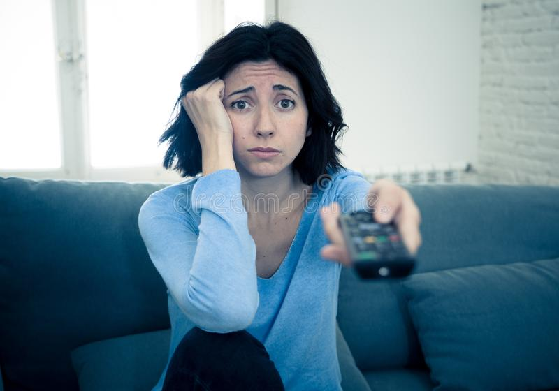 Bored woman changing TV channels with remote control. Young upset woman on sofa using control remote zapping bored of bad TV shows and programing . Looking royalty free stock photos