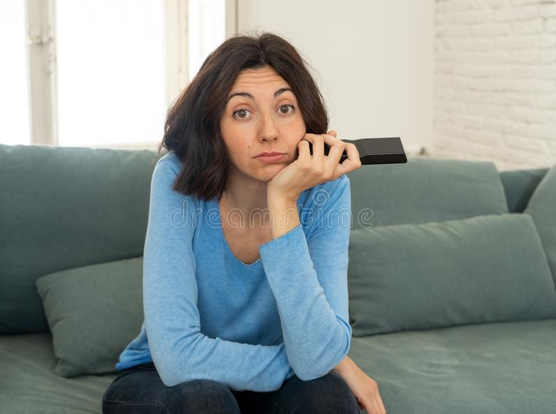 Bored woman changing TV channels with remote control. Young upset woman on sofa using control remote zapping bored of bad TV shows and programing . Looking stock photo