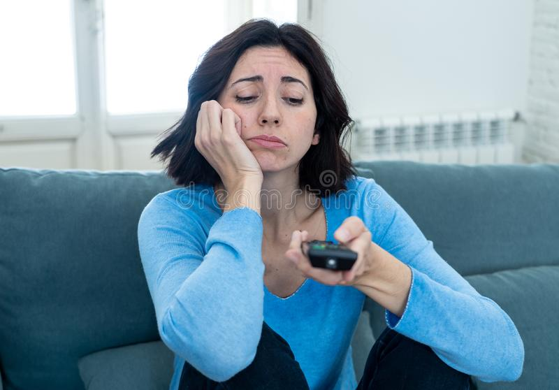 Bored woman changing TV channels with remote control. Young upset woman on sofa using control remote zapping bored of bad TV shows and programing . Looking stock images