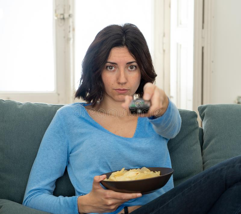 Bored woman changing TV channels with remote control. Young upset woman on sofa using control remote zapping bored of bad TV shows and programing . Looking stock photos